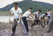 North Korean workers build levees along a river bank