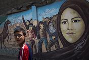 Palestinian boy walks past a graffiti in Gaza City