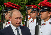 Russia's President Vladimir Putin walks past honour guards during his visit to Singapore