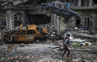 A boy rides his bike past destroyed cars and houses in a neighborhood recently liberated by Iraqi security forces, on the western side of Mosul, Iraq, March 19