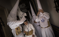 "Hooded penitents from ""La Candelaria"" brotherhood preparing inside their house before taking part in a procession in Seville, Spain"