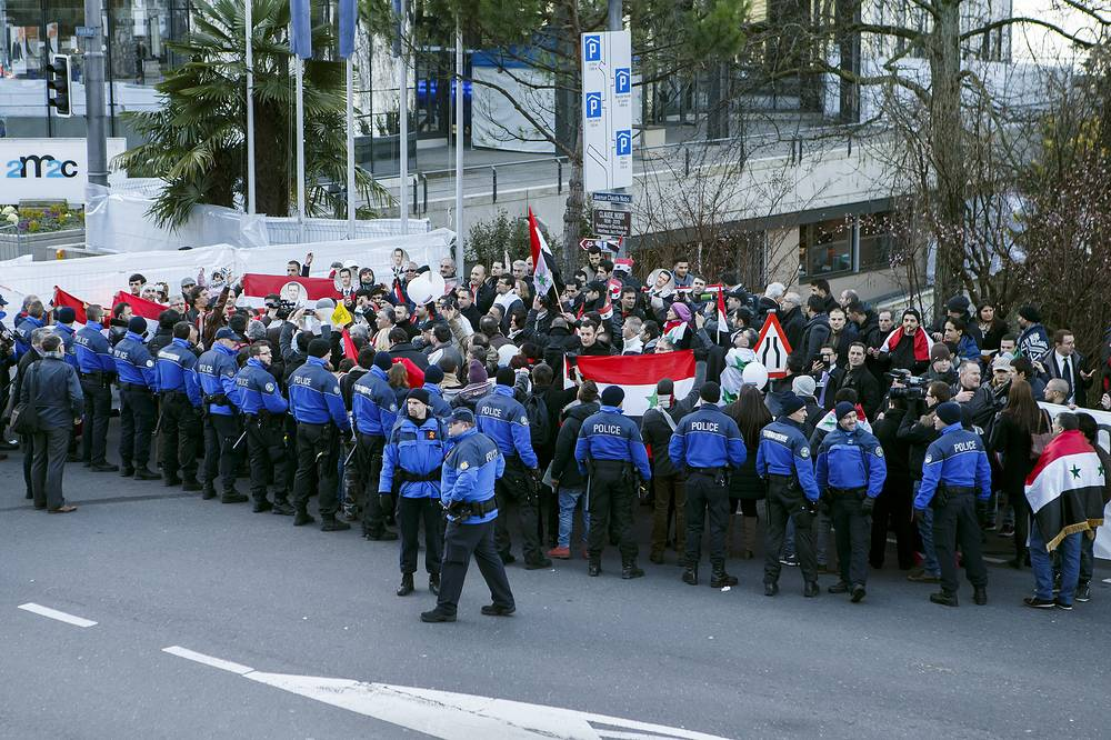 Pro Syrian President Bashar al-Assad supporters protest near the hotel, during the opening of the Geneva II peace talks, in Montreux