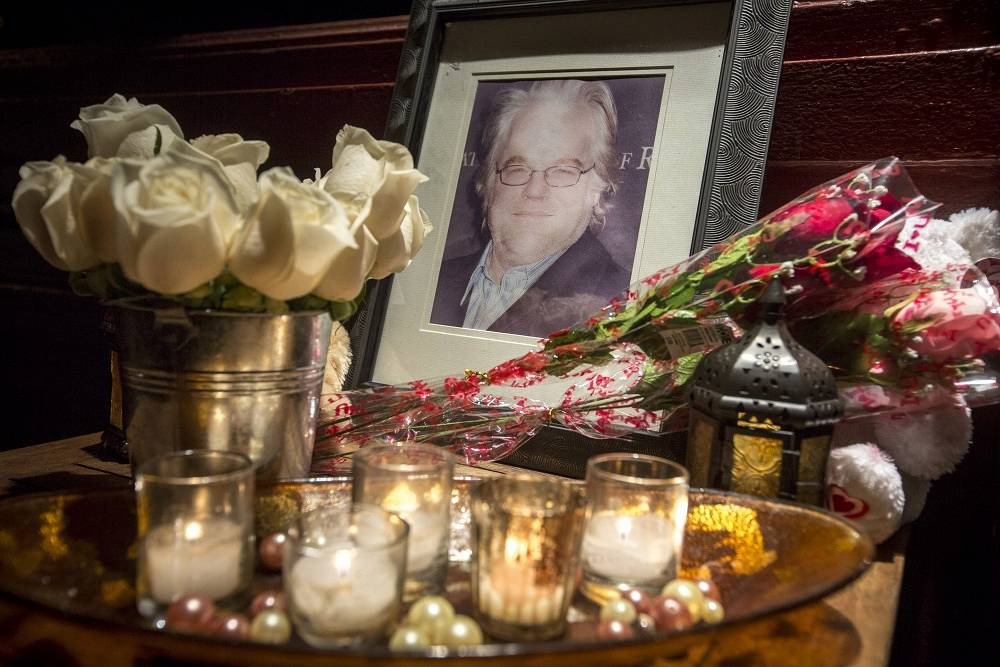 The portrait of Filip Seymour Hoffman near the building he was found in. People leave flowers and candles to honor his memory