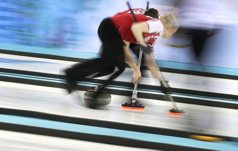 Russia's Alexandra Saitova, foreground, and Ekaterina Galkina sweep the ice during the women's curling competition against the United States