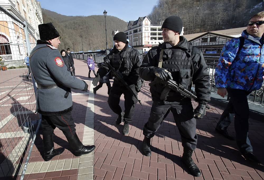 Russian security forces shake hands with a Cossack as they patrol the streets