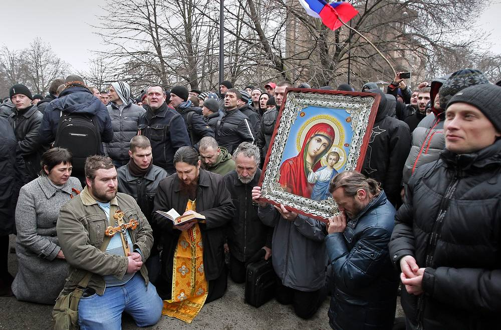 Pro-Russian activists pray near the Crimean Parliament building in Simferopol