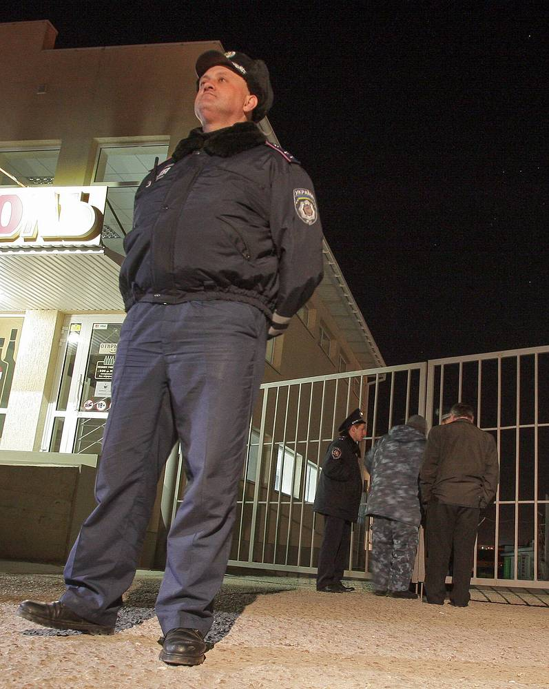 A Crimean policeman patrols at the gates of an Ukrainian military unit where the shooting incident took place