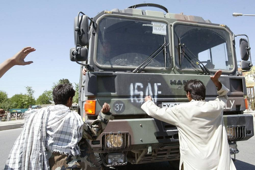 NATO heads the ISAF international security mission in Afghanistan in 2003. Photo: students stopping a NATO truck during a protest against introduction of troops