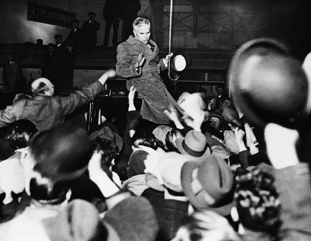 Chaplin cheers his fans at a railway station in London