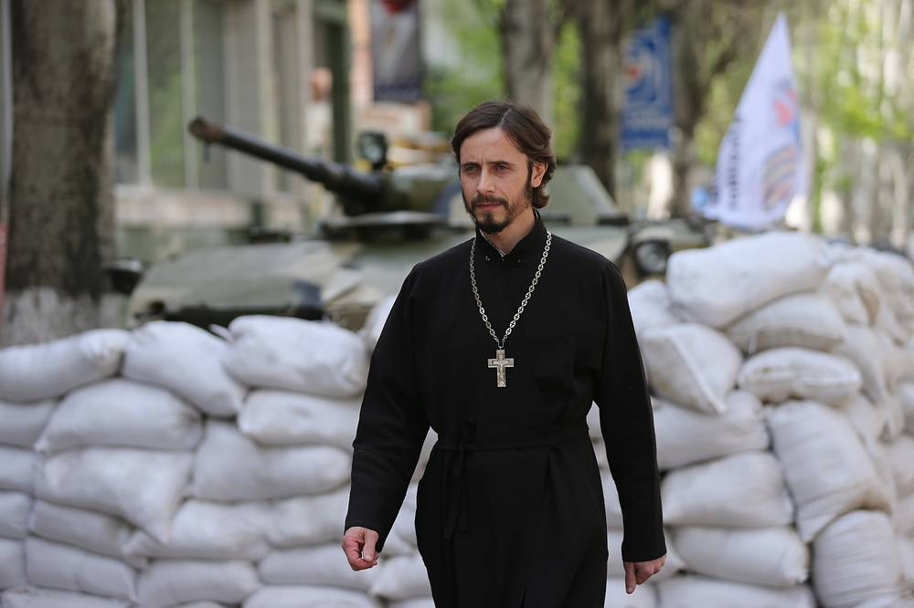 A priest passes a barricade in Sloviansk
