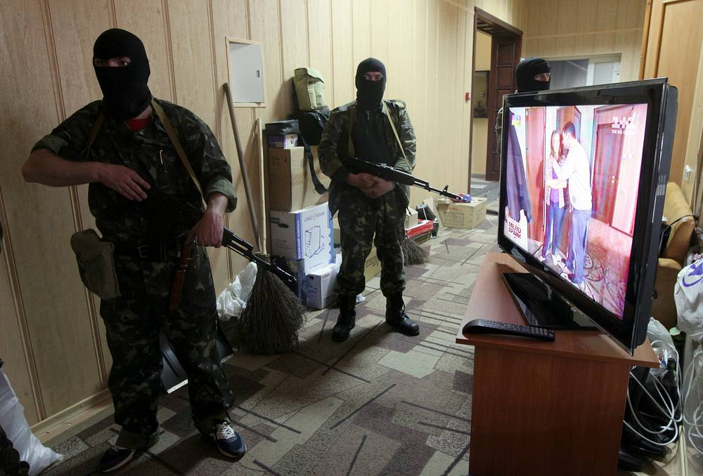 Armed men stand next to a TV set as they guard the entrance of the occupied Office of Public Prosecutor