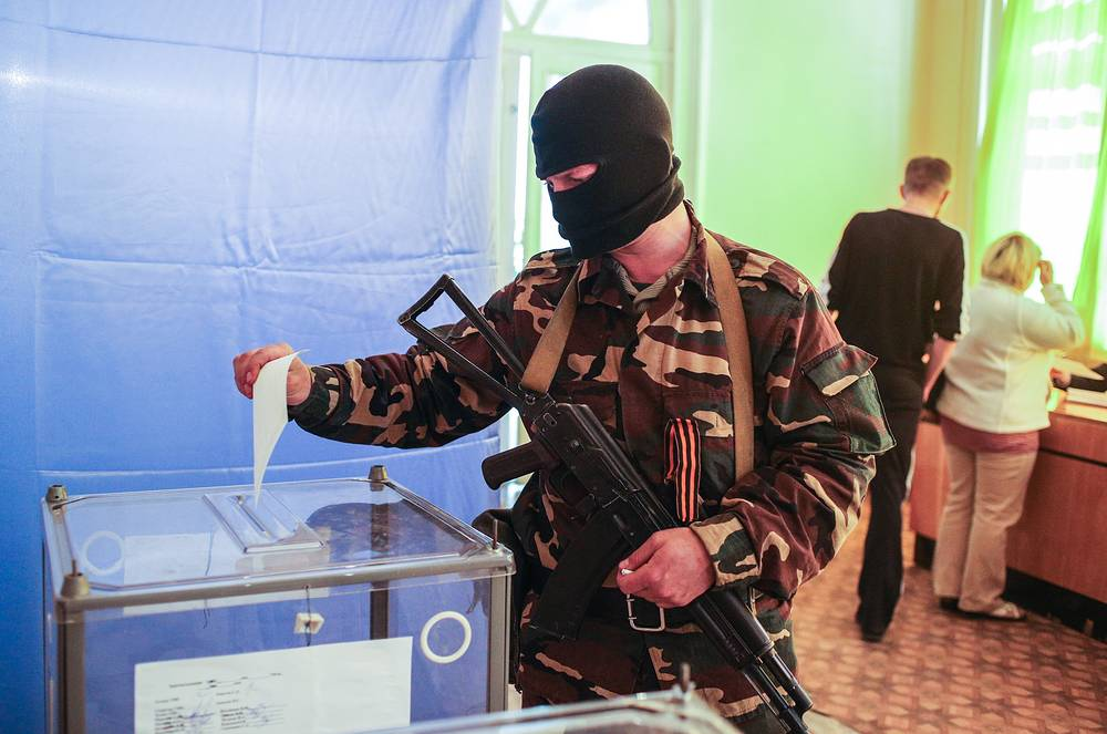 an armed activist votes at a referendum in Sloviansk, Donetsk region