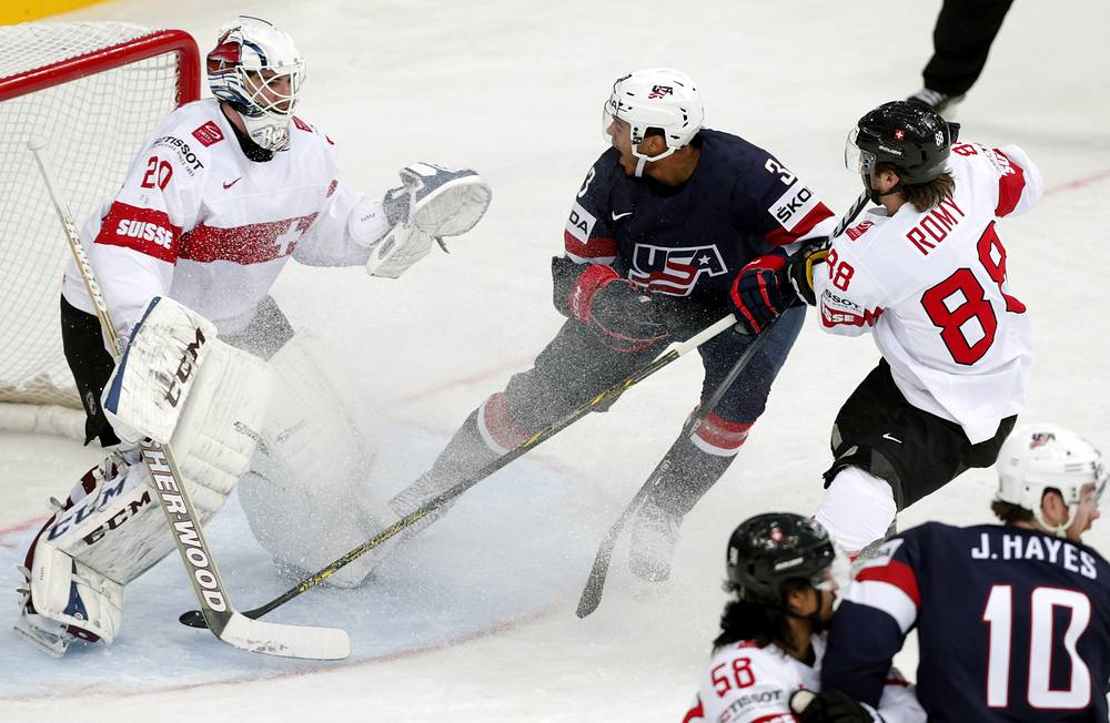 Seth Jones (C) of USA in action against Swiss player Kevin Romy (R)
