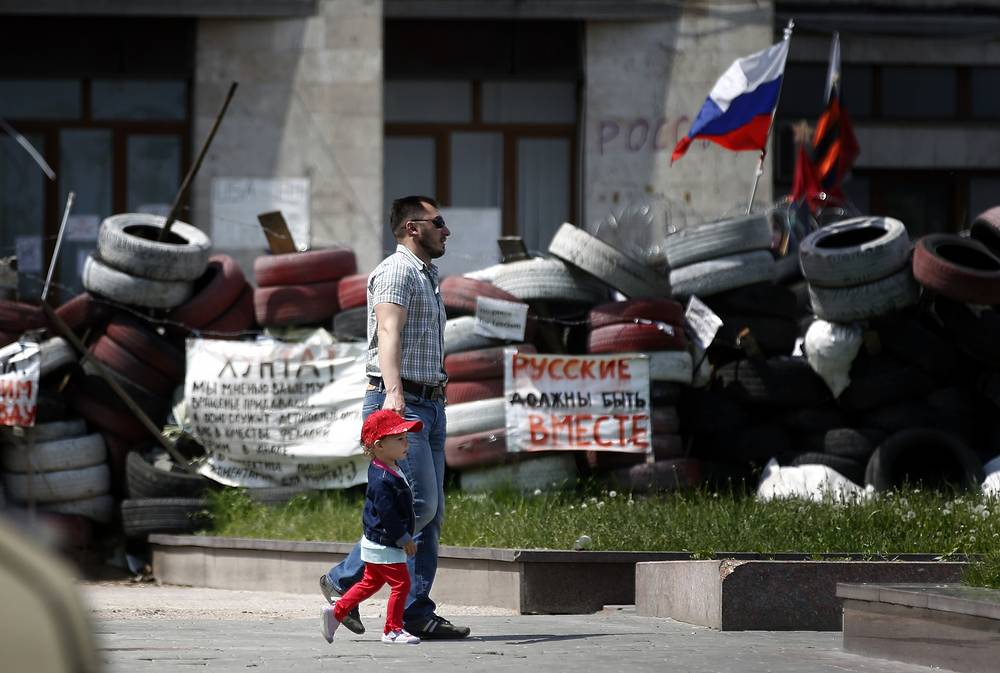 A man with child walk along a barricade in front of an administration building in Donetsk