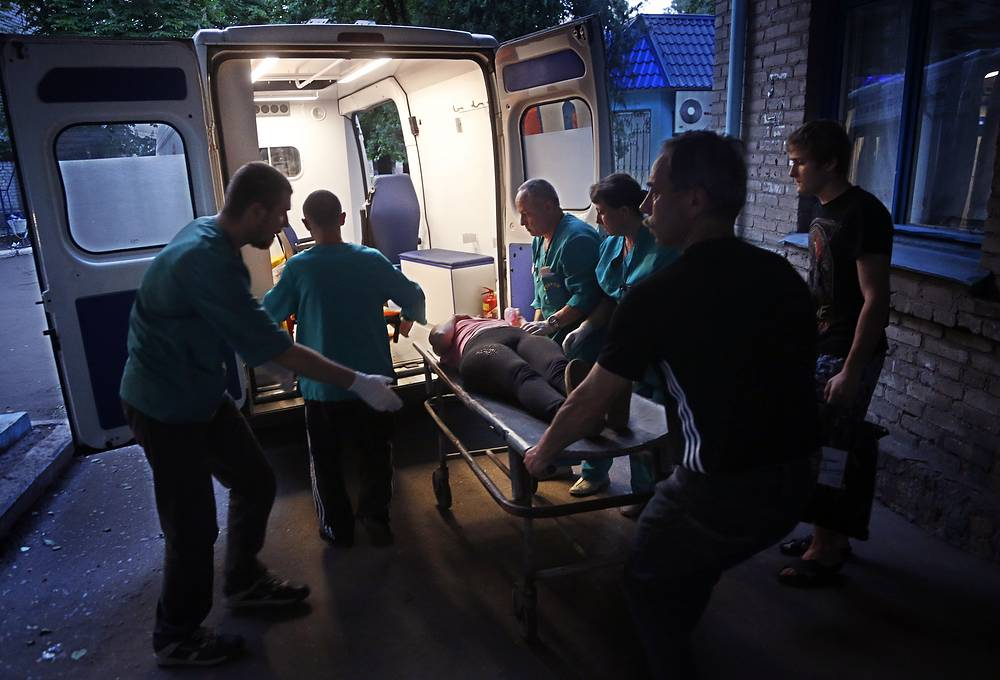 Medics carry a local woman injured in a shell explosion in Sloviansk