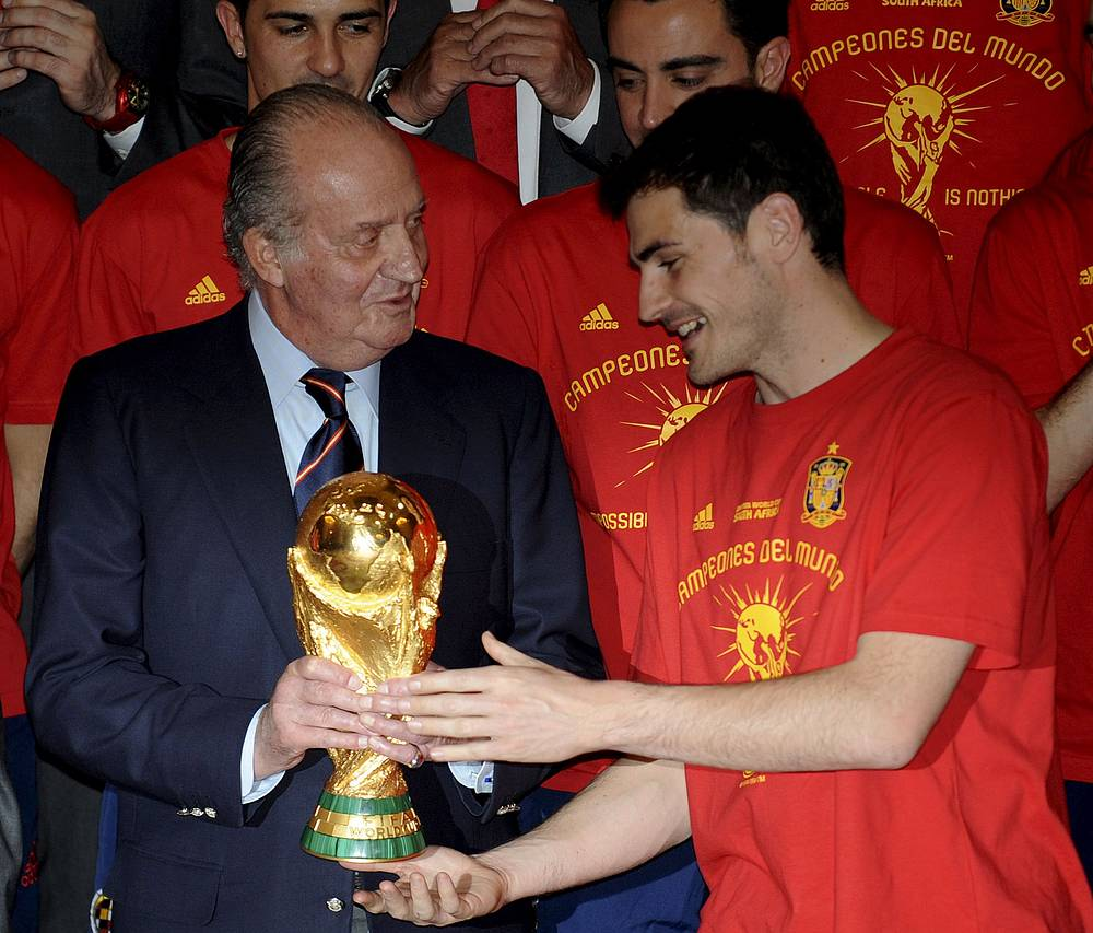Spanish national soccer team goalkeeper Iker Casillas (R) hands the World Cup trophy to Spanish King Juan Carlos in 2010