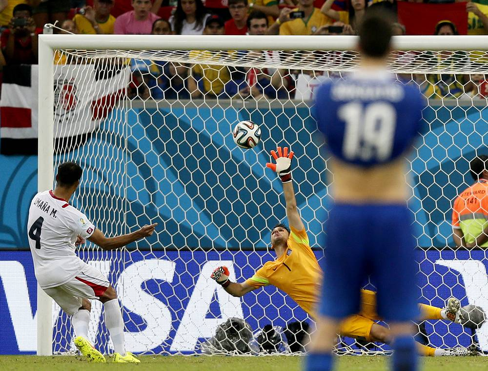 Michael Umana (L) of Costa Rica scores the decisive penalty