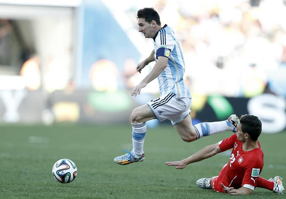 Lionel Messi (L) of Argentina in aciton against Fabian Schaer of Switzerland