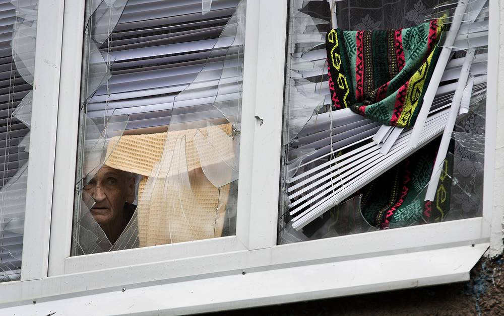 A local looks out of a window in Sloviansk