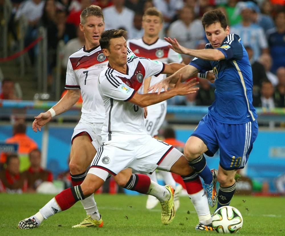 Germany's Mesut Ozil is trying to hold back Argentina's Lionel Messi