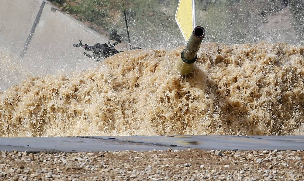 The tank of Kuwait's team drives through a water obstacle