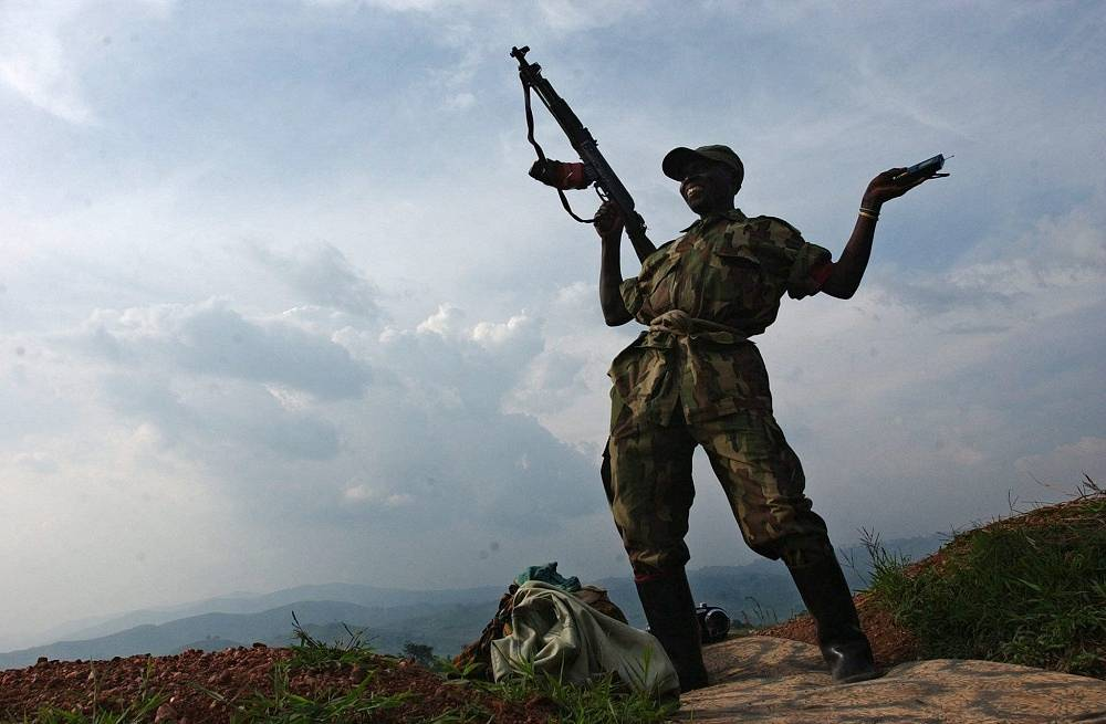 Photo: A renegade soldier dances with his Kalashnikov and a radio on a front line trench overlooking the the town of Karumba in the Democratic Republic of Congo