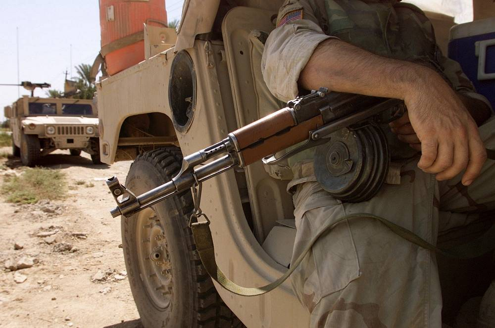 Photo: A US Army soldier holds a Kalashnikov rifle in Baqouba, Iraq, 2003