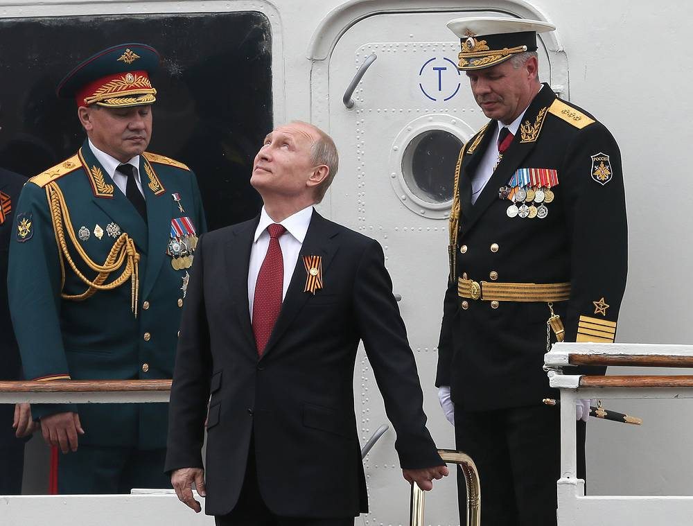 Russian President Vladimir Putin (center) watches a naval and aircraft parade celebrating Victory Day and the 70th anniversary of Sevastopol's liberation from Nazi forces