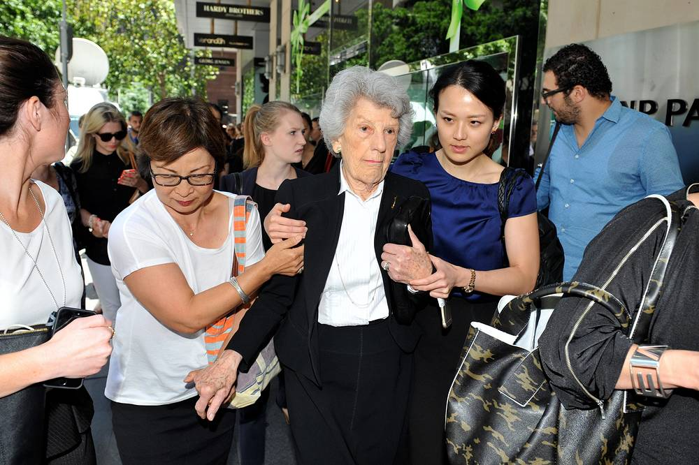 Photo: An elderly women is helped to evacuate during a siege under way in the central business district of Sydney, 15 December 2014