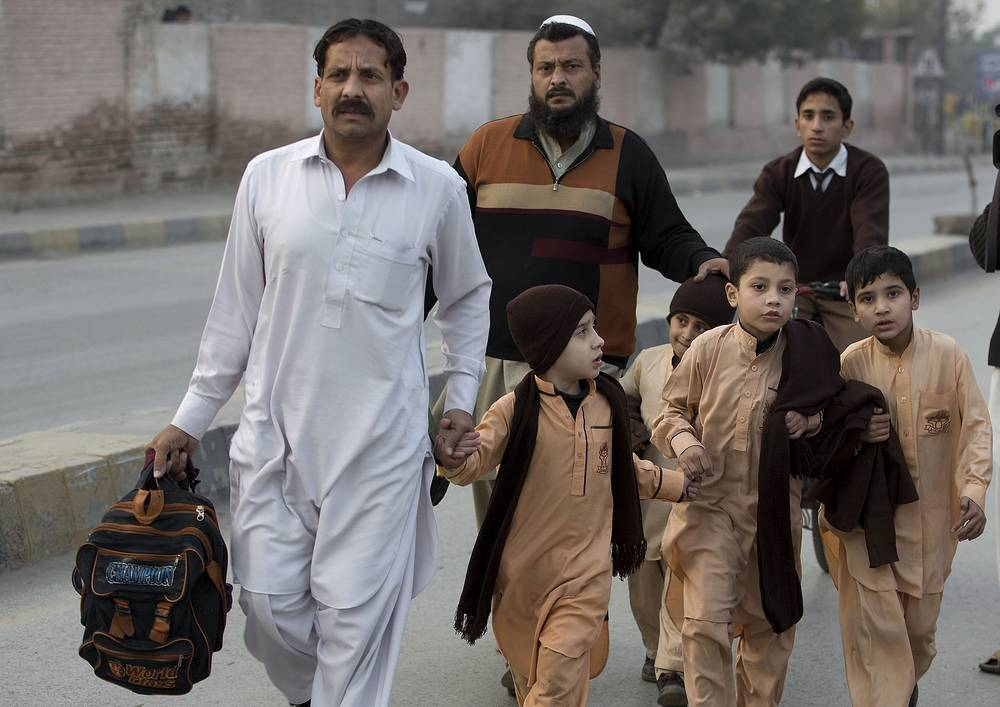 Photo: Pakistani parents escort their children outside a school attacked by the Taliban in Peshawar