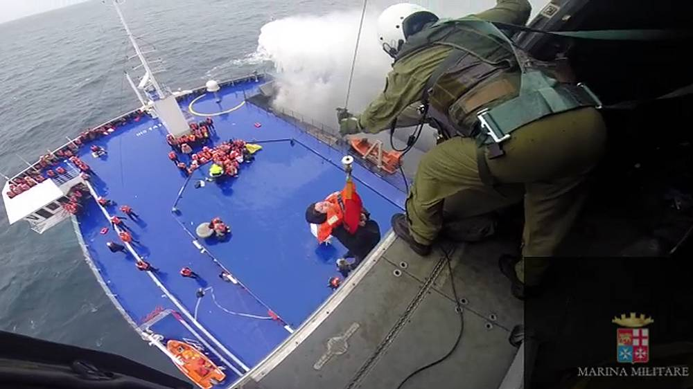 An Italian coast guard ship, ten freight ships, Italian helicopter carrier are participating in the rescue operation. Photo: Woman is lifted from the deck of the ferry Norman Atlantic by a rescue helicopter