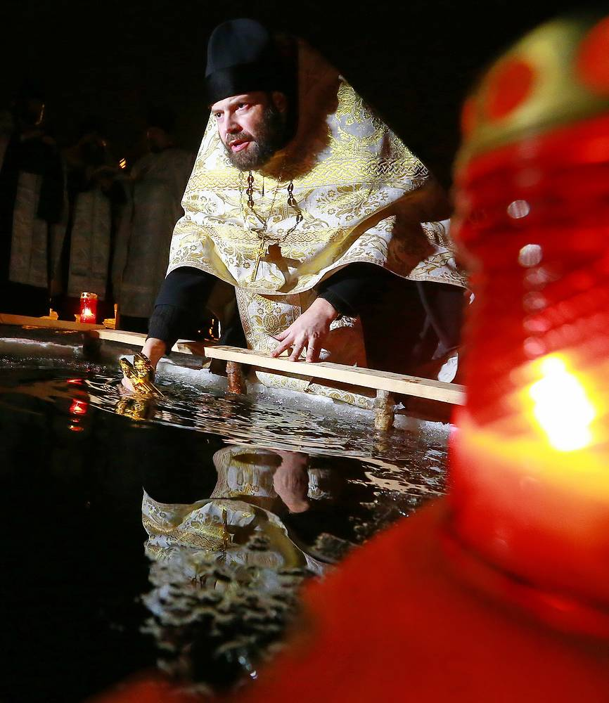 A priest blesses an ice-hole during the celebrations of the Orthodox Epiphany in Ivanovo region