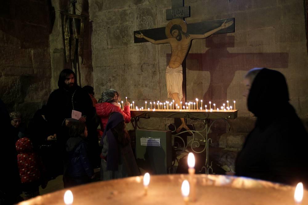 Georgian Orthodox believers pray during Epiphany celebrations at the Svetitskhoveli Cathedral in Mtskheta, Georgia