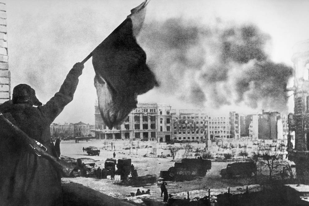 Soviet soldier waving Soviet Banner of Victory over the central square in Stalingrad