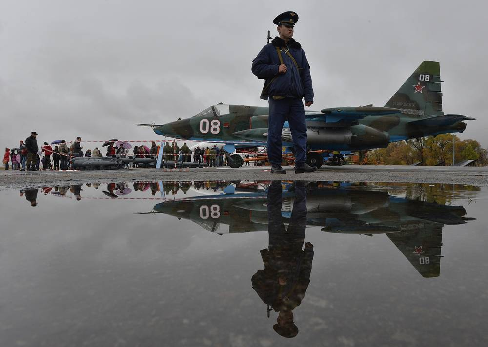 Photo: Russian officer guard patrols at Kant, a Russian air base, outside Bishkek, Kyrgyzstan, with a Su-25 ground attack jet parked is in background