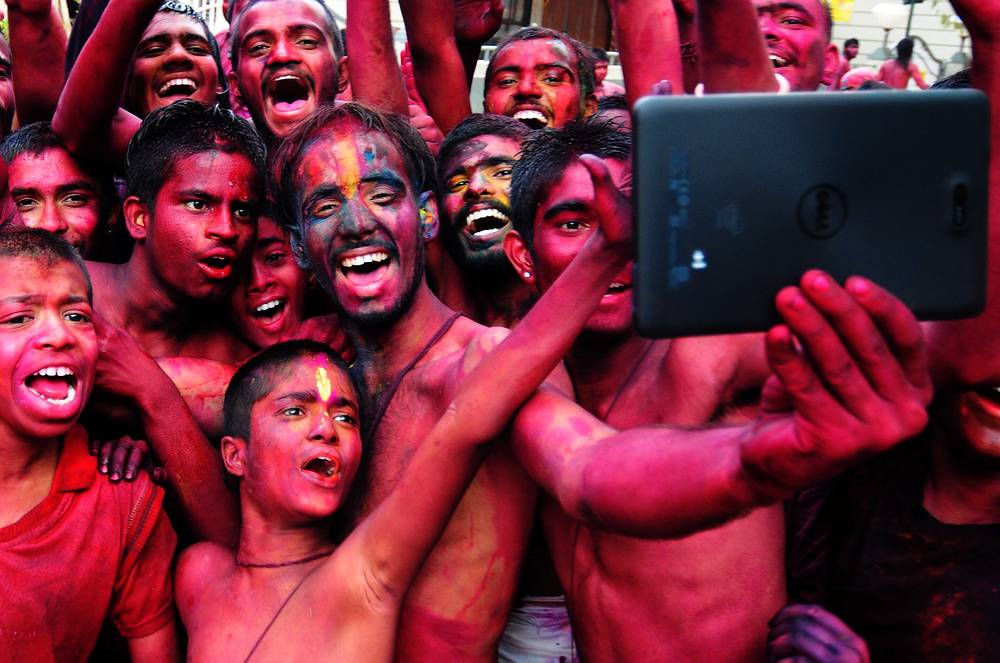 Indian revellers smeared with colors taking selfies during the Holi Festival in Bangalore, India
