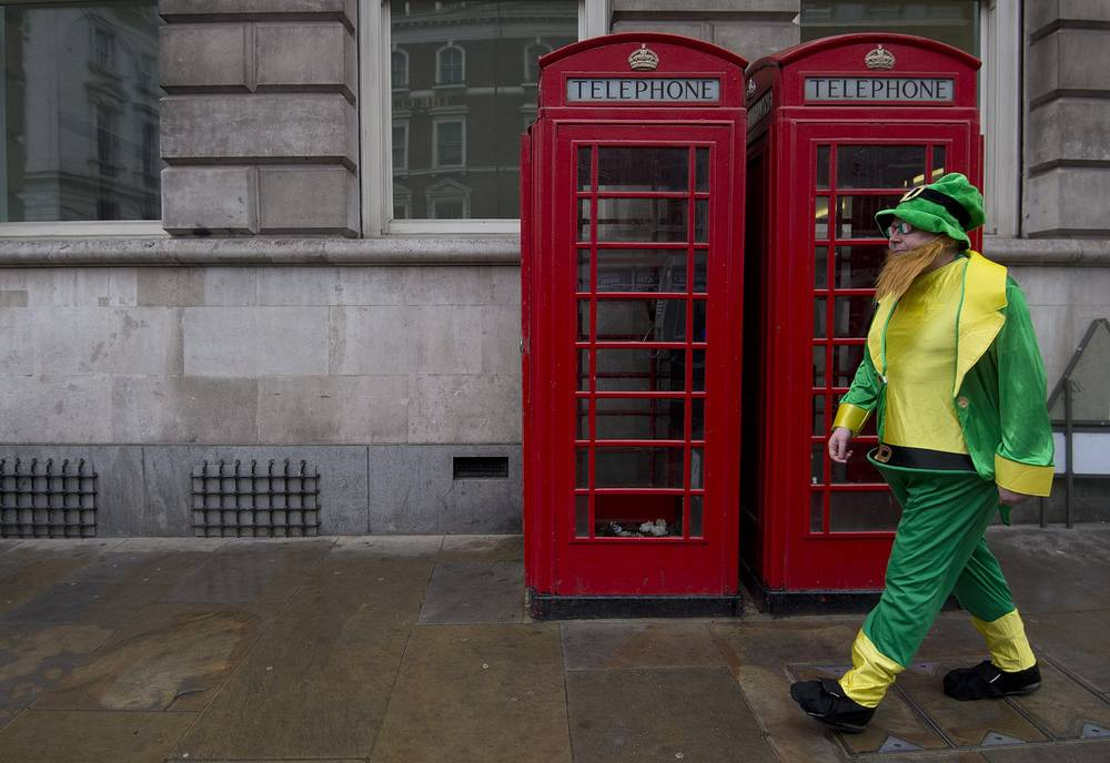 A man dressed as a leprechaun, a fairy type in Irish folklore, walking past telephone boxes during the St. Patrick's Day Parade in London, Britain