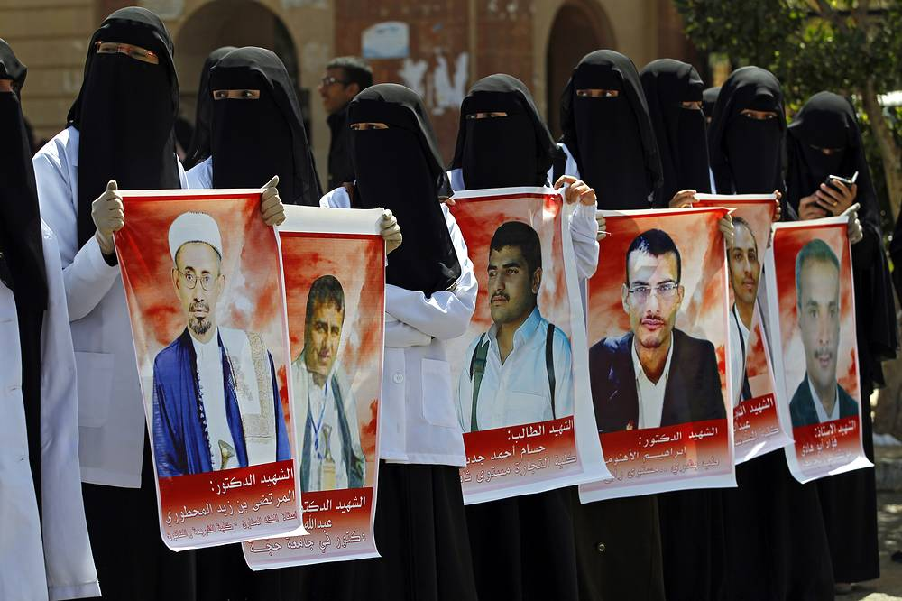 University students with posters bearing the portraits of victims of the recent suicide attacks, during an anti-terrorism rally in Sana'a, Yemen, 22 March 2015