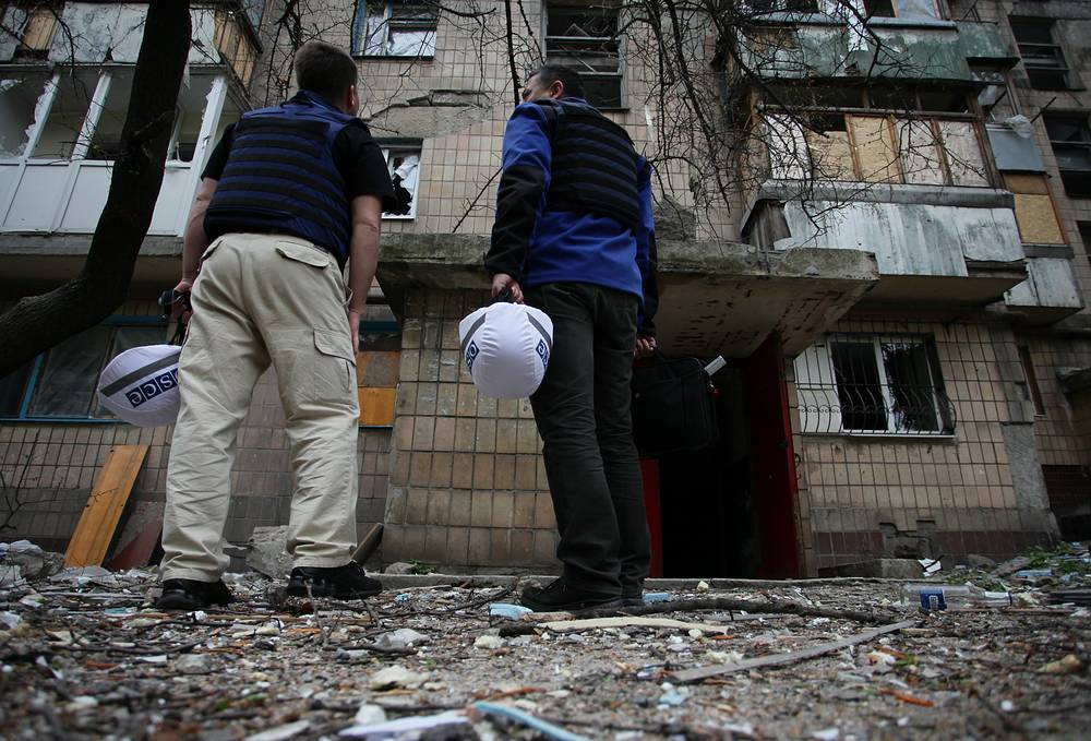 OSCE employees near the building damaged during a shelling attack in Donetsk's Kievsky District