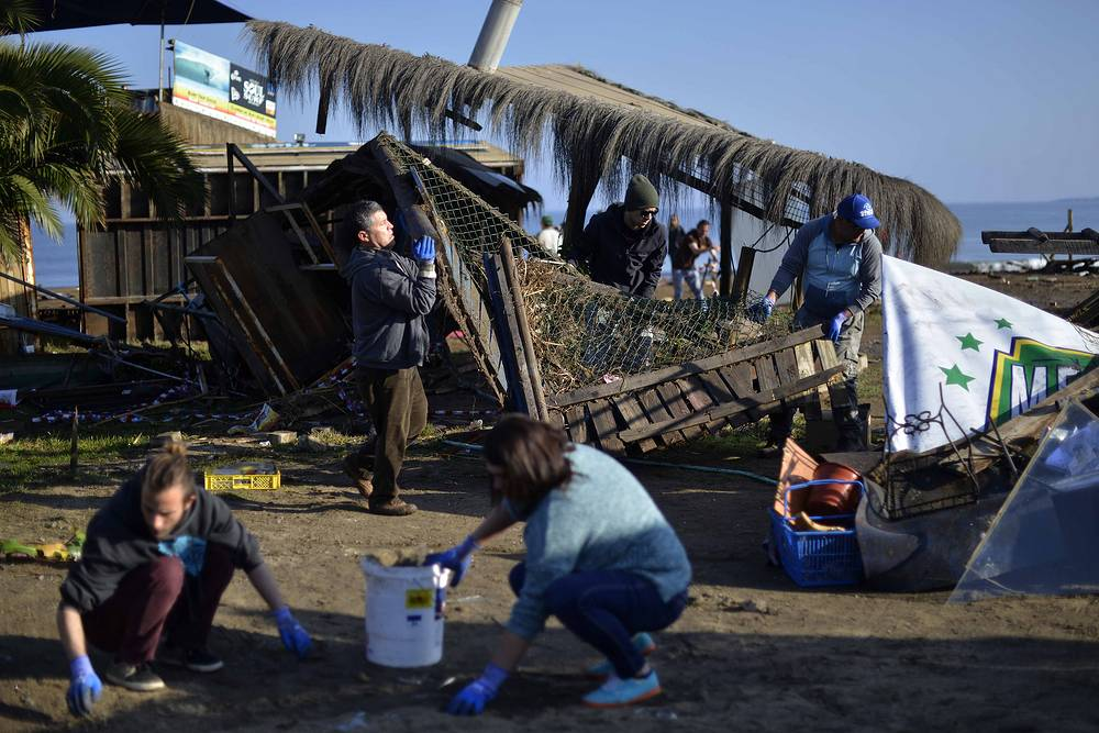 People cleaning the beach after an earthquake-triggered tsunami damaged homes and businesses in Concon, Chile