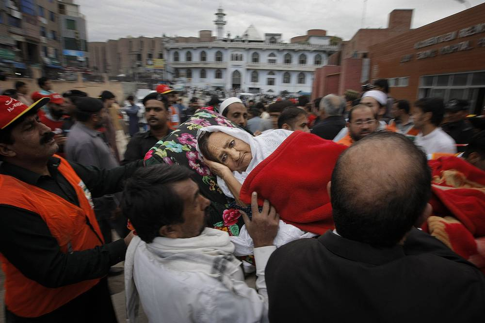 People rushing an injured woman to a local hospital in Peshawar, Pakistan