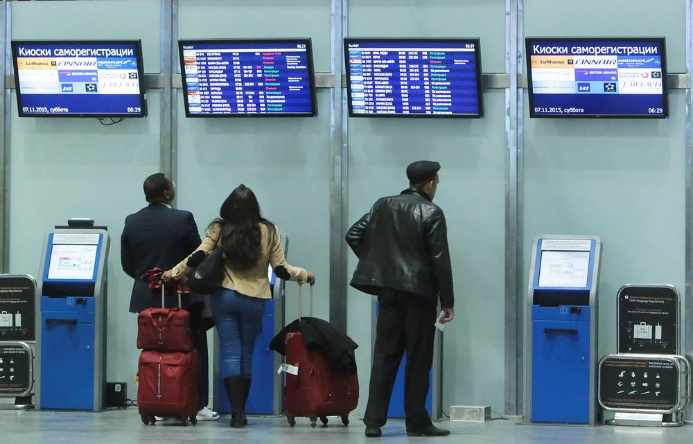 Passengers looking at flight schedule boards at Pulkovo International airport in St. Petersburg