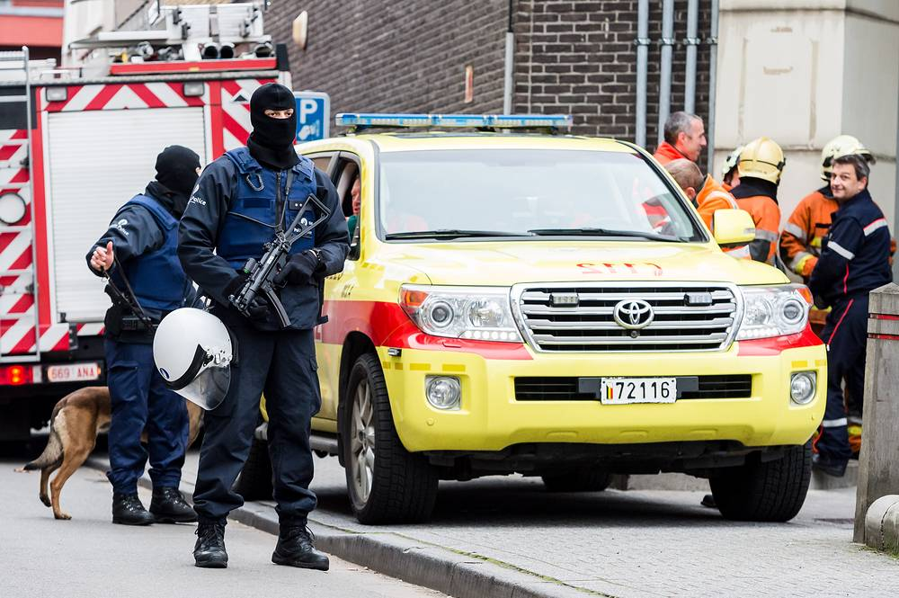 Armed police seen in the Brussels neighborhood of Molenbeek amid a manhunt for a suspect of the Paris attacks
