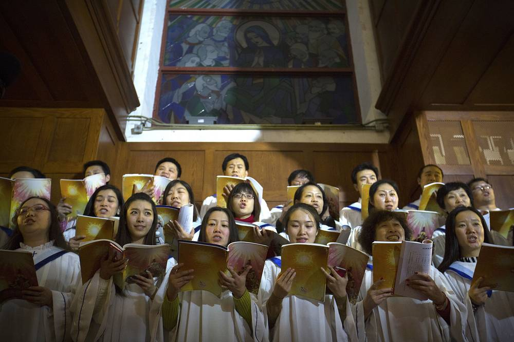 Chinese choir members singing during a Christmas Eve mass at the Southern Cathedral, an officially-sanctioned Catholic church in Beijing, China