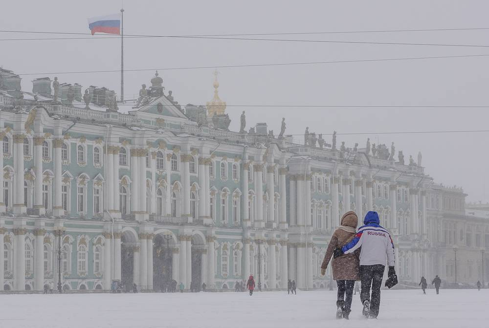 People walking in Palace Square during a heavy snowfall in Saint Petersburg