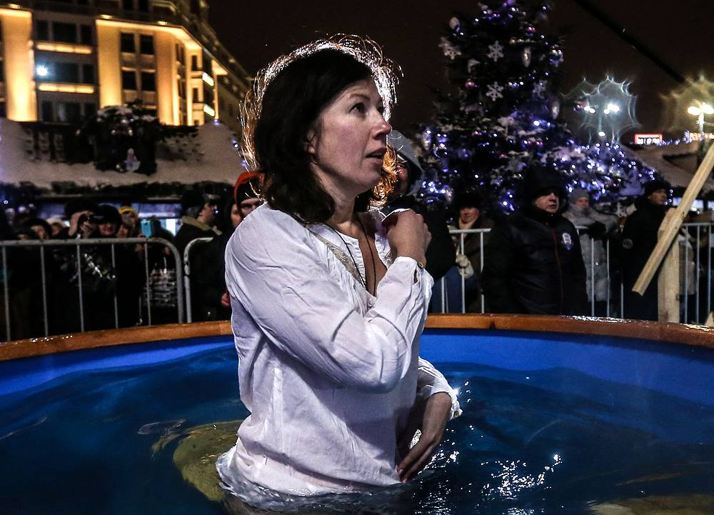 A girl dips into a basin of cold water in Moscow's Revolution Square