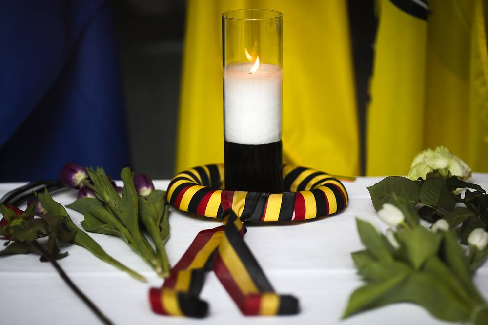 A candle wrapped in a ribbon in the colors of the Belgium national flag and flowers are placed on a table inside the Belgium Embassy in Berlin, Germany