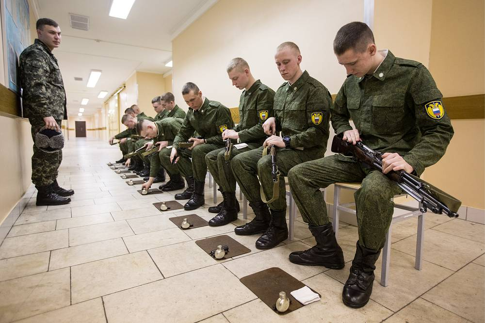 Servicemen of the Presidential Regiment cleaning their rifles
