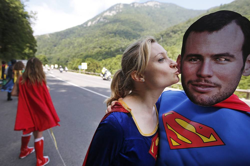 Fans wearing a mask with the face of Britain's sprinter Mark Cavendish