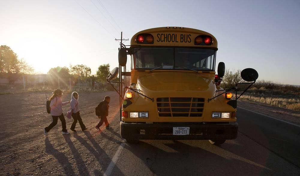 School children walking to board a school bus at Fort Hancock, Texas, USA